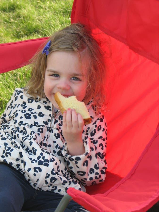 Ragazza che mangia un panino fotografia stock libera da diritti
