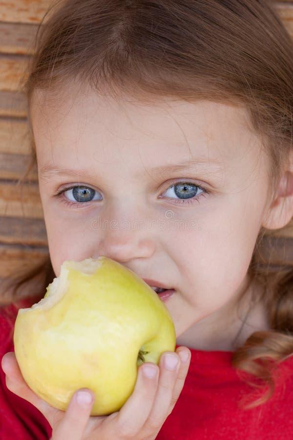 Ragazza che mangia una mela immagini stock libere da diritti