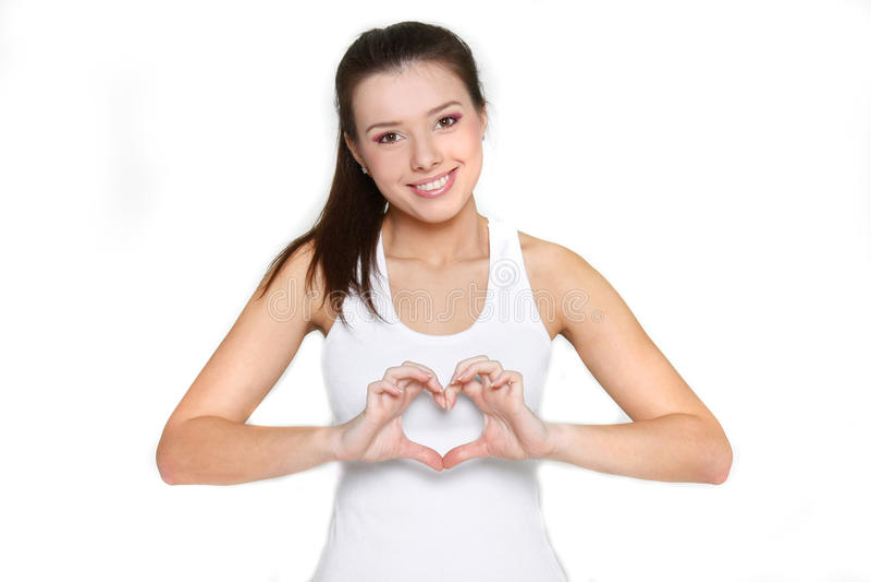 Ragazza che mostra simbolo del cuore sopra bianco immagine stock libera da diritti