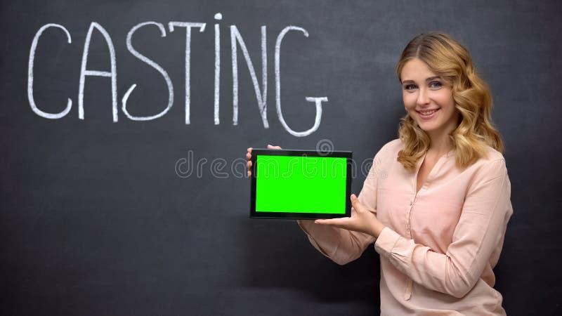 Ragazza che offre la registrazione online per il casting, con tavoletta con schermo verde immagine stock libera da diritti