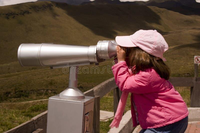 Ragazza che osserva con il binocolo fotografia stock