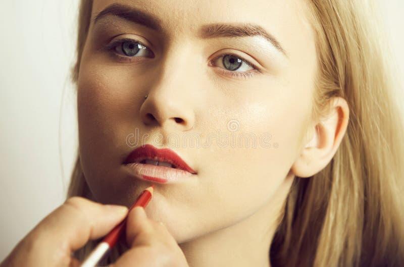 Ragazza che ottiene matita rossa sulle labbra dalla mano maschio fotografia stock