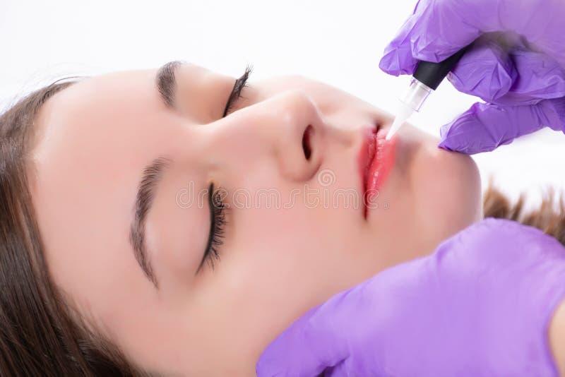 Ragazza che ottiene a tatuaggio le labbra rosse nello studio di bellezza Il cosmetologo professionale che rende permanente compon immagini stock