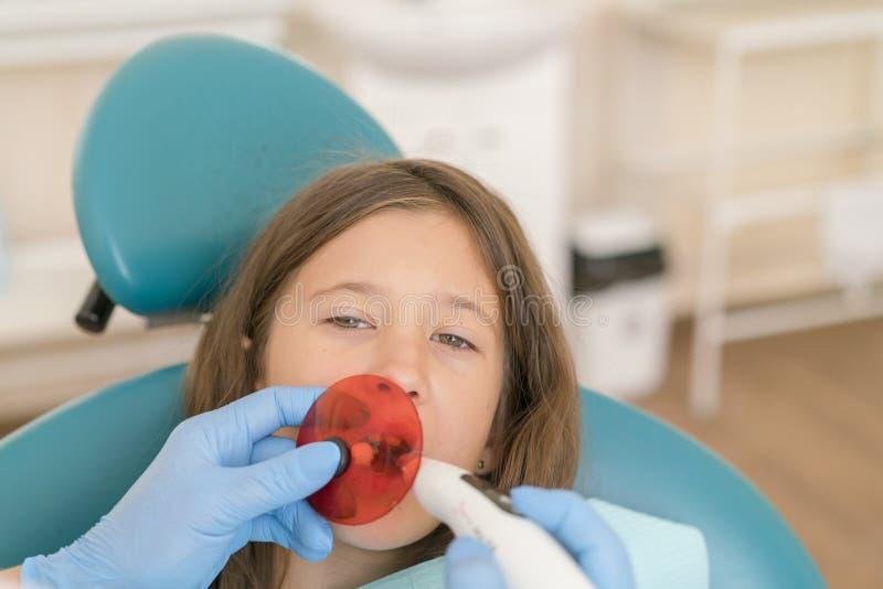 Ragazza che ottiene trattamento di riempimento dentario al dente molare con tecnologia ultravioletta Immagine della bambina che f immagine stock libera da diritti