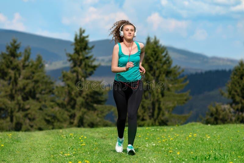 Ragazza che pareggia sulla traccia in montagne sul campo con erba nel giorno soleggiato di estate immagine stock libera da diritti