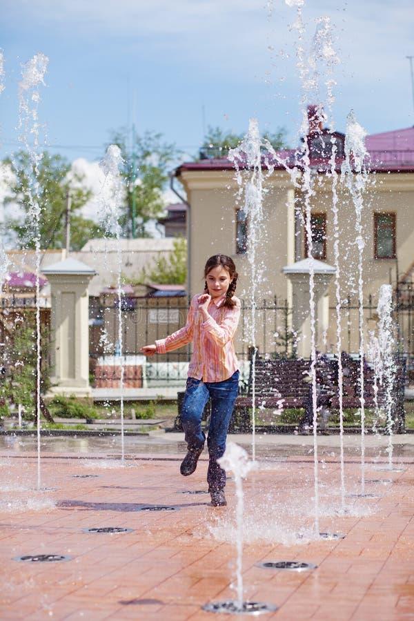 Ragazza che passa i getti di acqua in una fontana fotografia stock libera da diritti