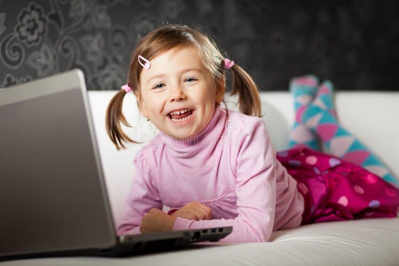Ragazza che per mezzo del computer portatile fotografie stock libere da diritti