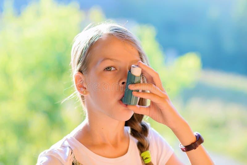 Ragazza che per mezzo dell'inalatore di asma fotografia stock