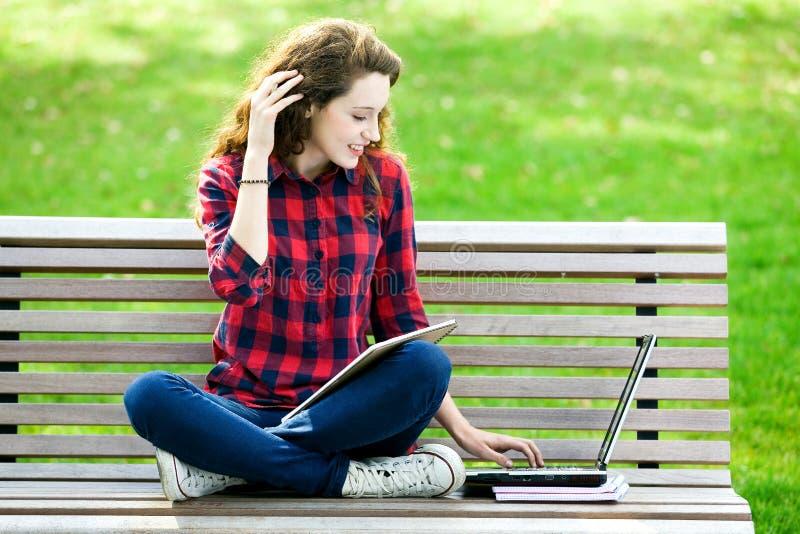 Ragazza che per mezzo di un computer portatile su un banco fotografie stock libere da diritti