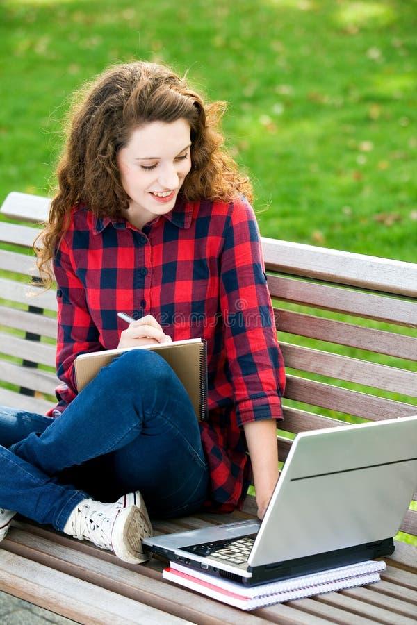 Ragazza che per mezzo di un computer portatile su un banco immagine stock libera da diritti