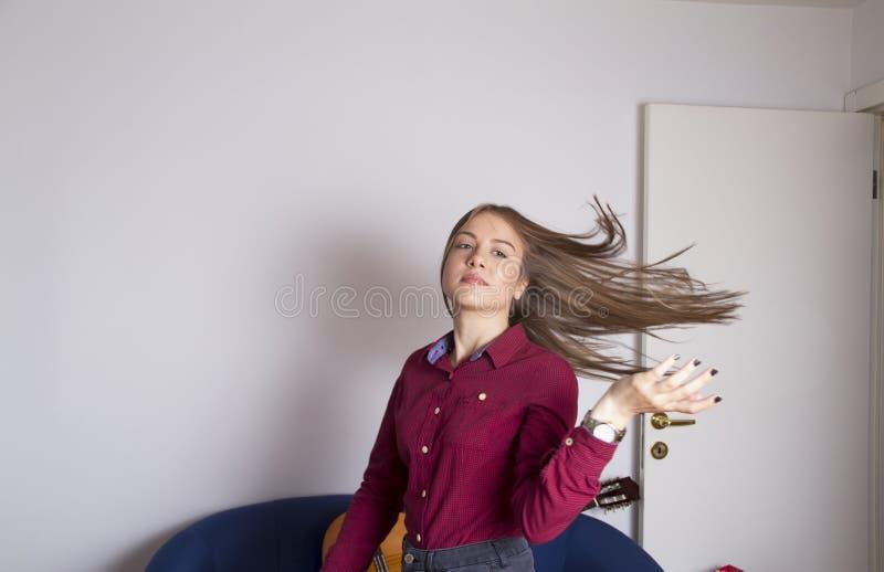 Ragazza che pilota i suoi capelli dal lato fotografia stock