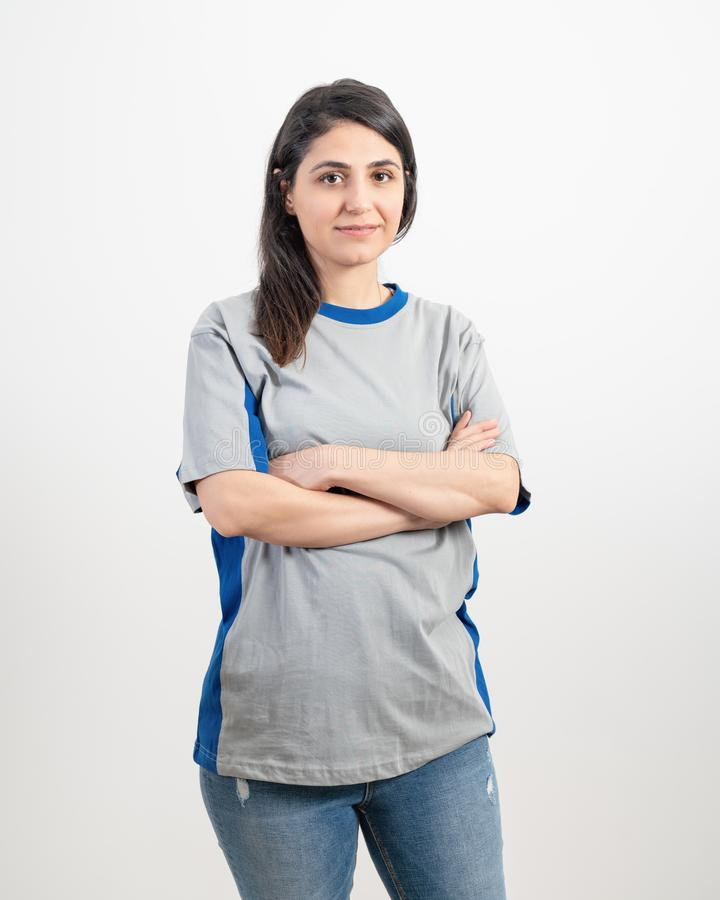 Ragazza che porta maglietta e le blue jeans grige in bianco Priorit? bassa grigia della parete fotografie stock