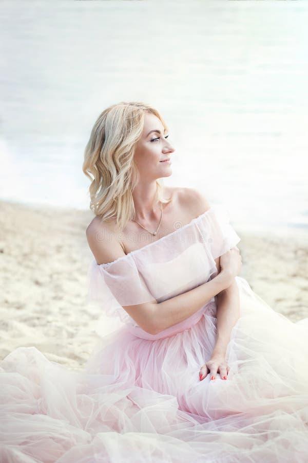 Ragazza che porta un vestito della Boemia lungo che si siede sulla spiaggia su un fine settimana di vacanza Una signora sola si s immagine stock libera da diritti