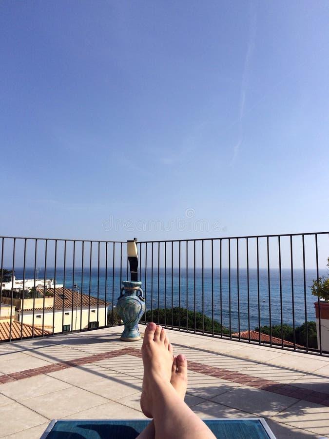 Ragazza che prende il sole al tetto con seaview fotografia stock libera da diritti