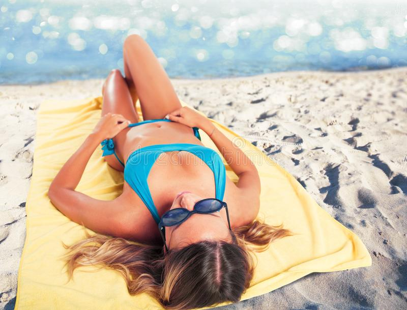 Ragazza che prende il sole sulla spiaggia sull'asciugamano Concetto di estate fotografia stock libera da diritti