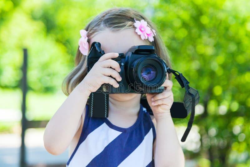 Ragazza che prende le immagini con una macchina fotografica della foto in parco immagini stock