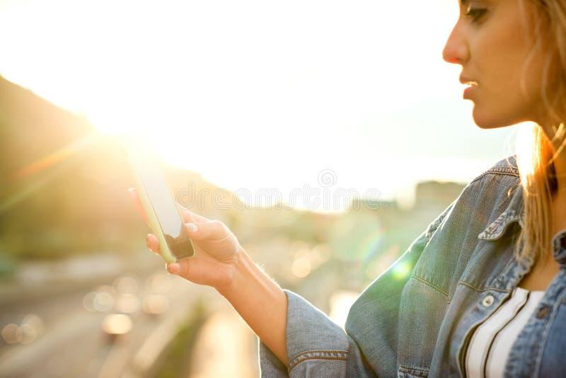 Ragazza che prende le immagini di un paesaggio, primo piano di un telefono in lei fotografia stock libera da diritti