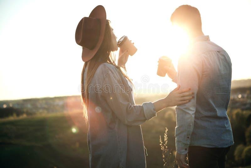 Ragazza che prende sorsata di caffè con il ragazzo durante il tramonto fotografie stock libere da diritti