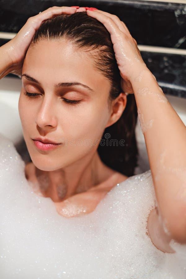 Ragazza che prende un bagno di bolla con gli occhi chiusi fotografia stock