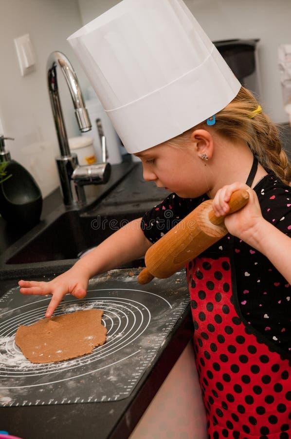 Ragazza che produce i biscotti del pan di zenzero immagini stock libere da diritti
