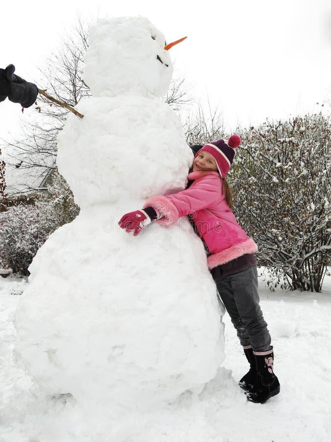 Ragazza che propone con il suo grande pupazzo di neve. immagini stock libere da diritti