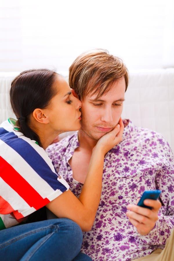 Ragazza che prova a distrarre il suo ragazzo dal mobile immagini stock