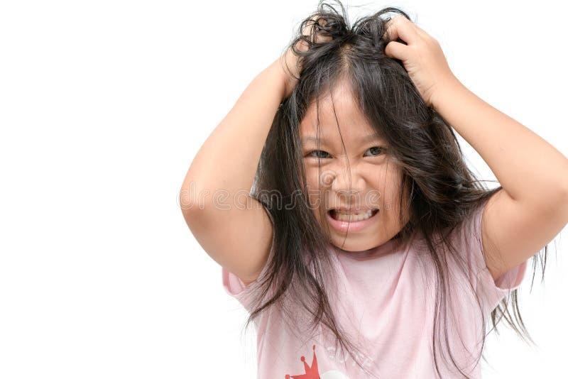 Ragazza che prude i suoi capelli o bambino frustrato ed arrabbiato fotografia stock