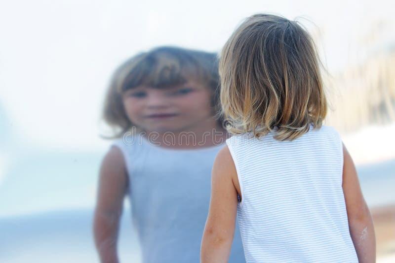 Ragazza che riflette in grande specchio immagine stock