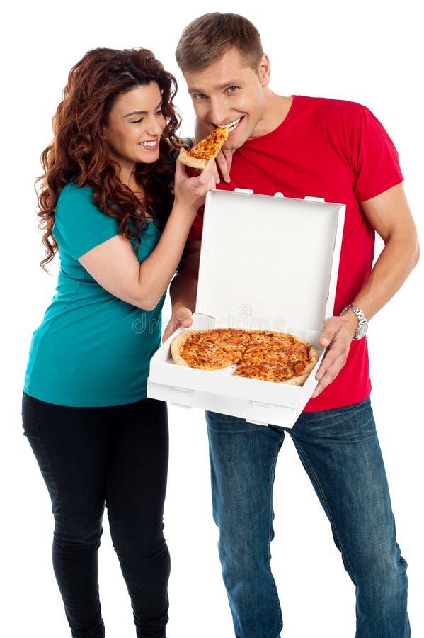 Ragazza che riparte una parte della pizza con il suo ragazzo fotografia stock