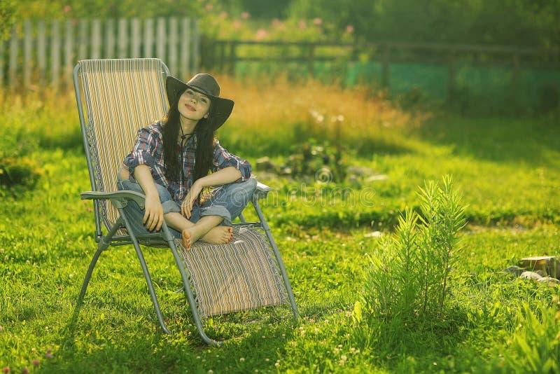 Ragazza che riposa su una chaise-lounge del sole fotografie stock