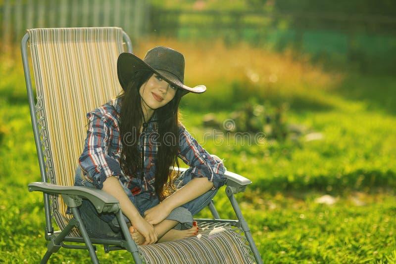Ragazza che riposa su una chaise-lounge del sole fotografia stock