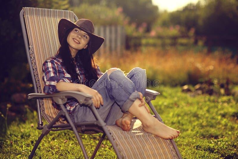 Ragazza che riposa su una chaise-lounge del sole immagine stock