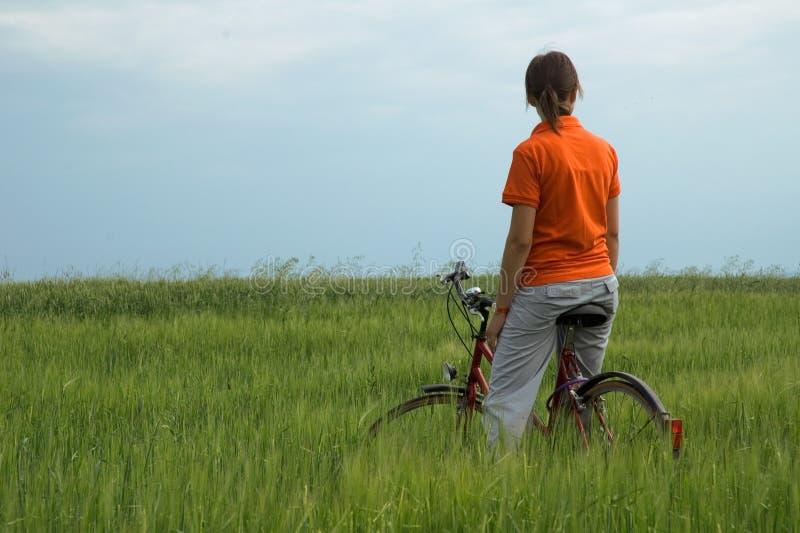 Ragazza che riposa sulla bicicletta nel campo verde fotografia stock