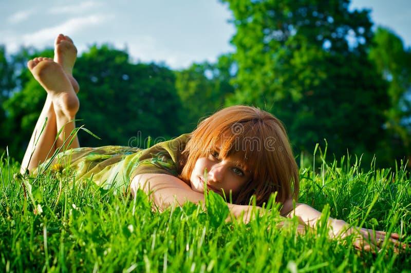 Ragazza che risiede nell'erba fotografia stock libera da diritti