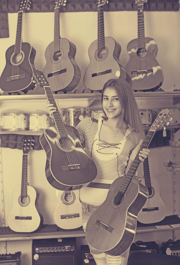 Ragazza che sceglie chitarra acustica immagine stock libera da diritti