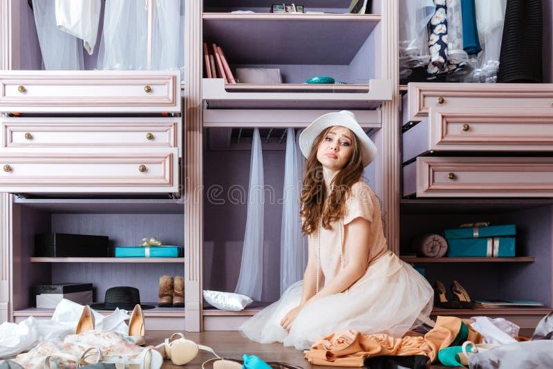Ragazza che sceglie i vestiti nel suo guardaroba fotografie stock