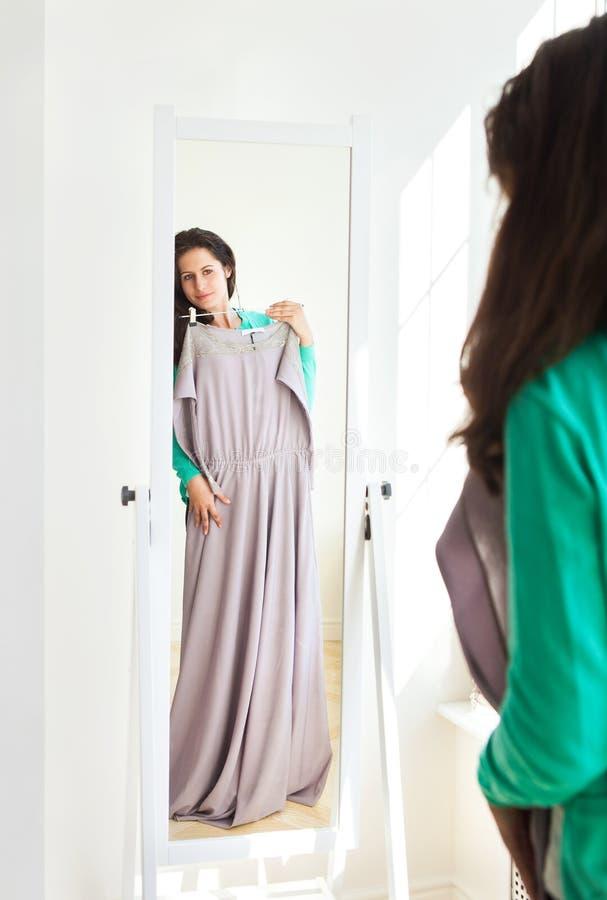 Ragazza che sceglie i vestiti in una sala d'esposizione fotografia stock libera da diritti