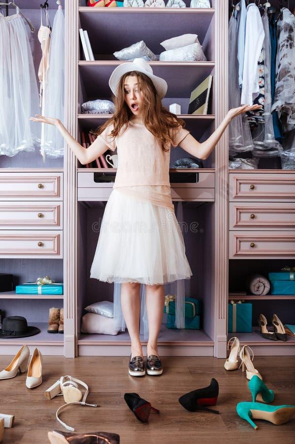 Ragazza che sceglie le scarpe nel suo guardaroba immagini stock