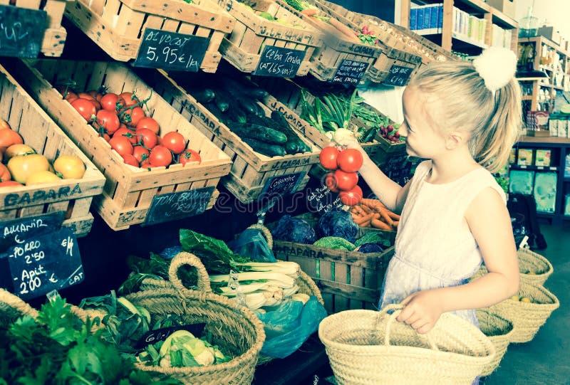 Ragazza che sceglie le verdure in negozio di verdure sull'Istituto centrale di statistica dell'insegna fotografia stock libera da diritti