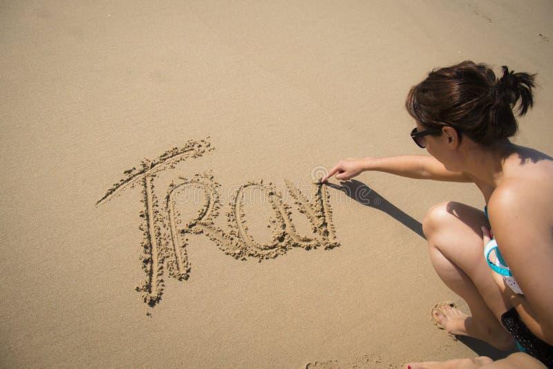 Ragazza che scrive il viaggio di parola nella sabbia fotografia stock