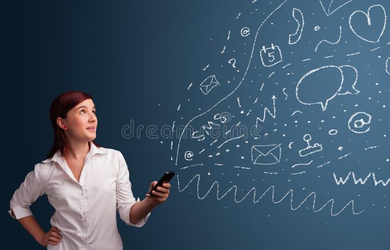 Ragazza che scrive sullo smartphone con le varie icone moderne di tecnologia immagini stock