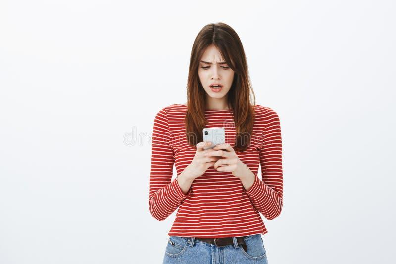 Ragazza che sembra colpita, vedendo i pirati informatici attaccare conto bancario Ritratto di giovane donna europea confusa preoc fotografia stock libera da diritti