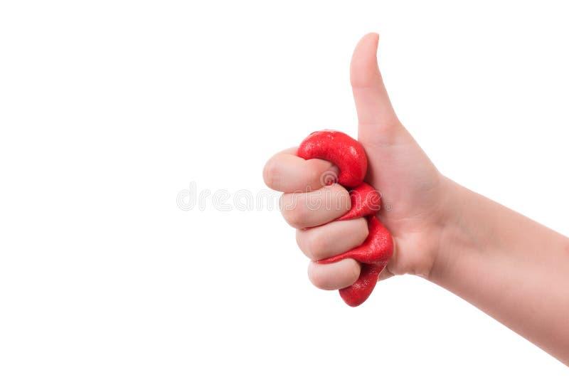 Ragazza che serra in un pugno una melma rossa su un fondo bianco immagine stock