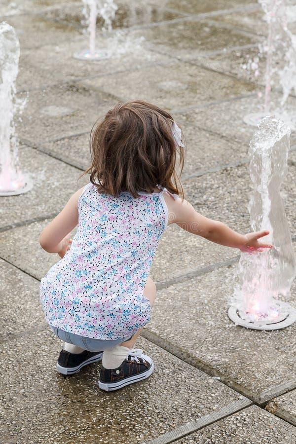 Ragazza che sguazza in una fontana un giorno di estate caldo fotografie stock libere da diritti