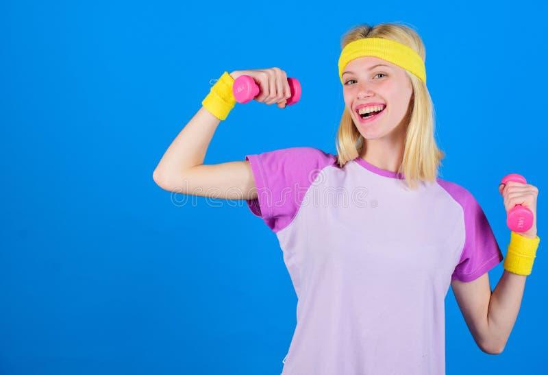 ragazza che si esercita con il dumbbell Istruttore di forma fisica tenere poco fondo blu della testa di legno Come ottenere costi immagini stock