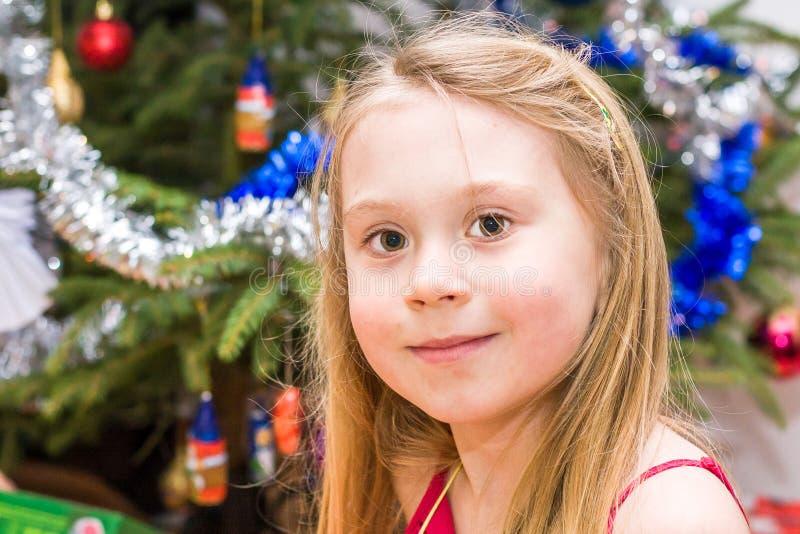 Ragazza che si leva in piedi davanti all'albero di Natale fotografia stock libera da diritti