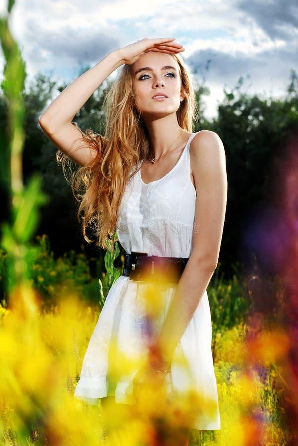 Ragazza che si leva in piedi su un glade e sugli sguardi del fiore dentro immagine stock