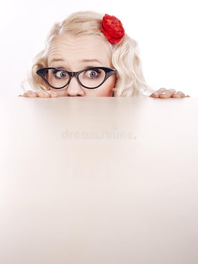 Ragazza che si nasconde dietro uno scrittorio fotografia stock