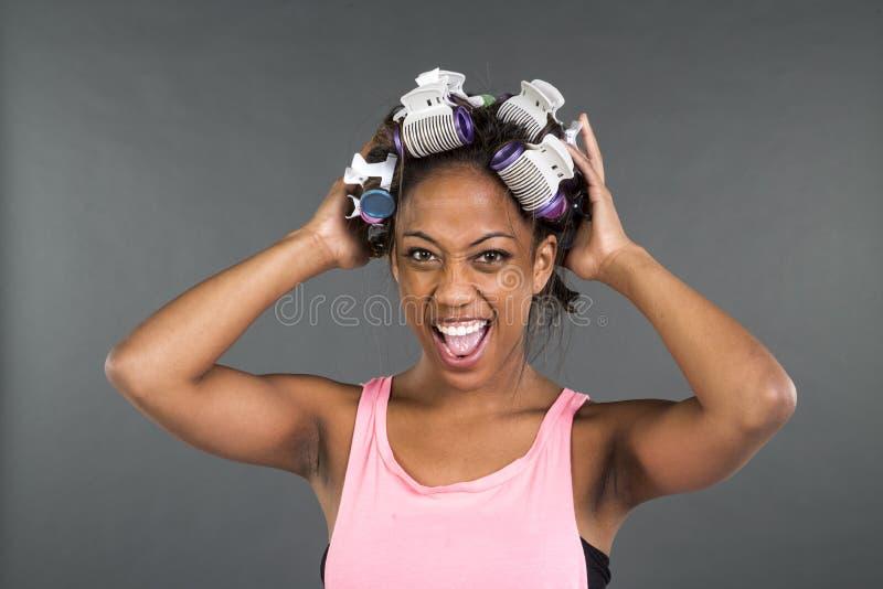 Ragazza che si prepara con i bigodini in suoi capelli fotografie stock