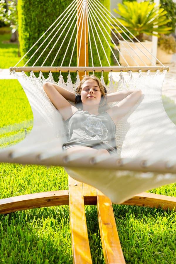 Ragazza che si rilassa e che ascolta la musica in amaca immagini stock libere da diritti